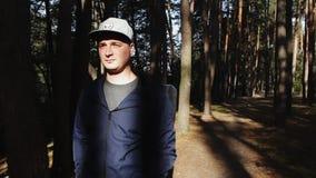 Uomo che cammina nell'alba nella foresta archivi video