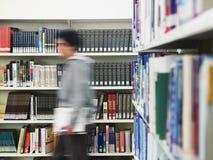 Uomo che cammina nella biblioteca Fotografie Stock