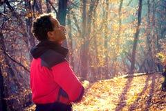 Uomo che cammina nella foresta di autunno Fotografie Stock