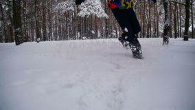 Uomo che cammina nella neve profonda nella foresta di inverno al giorno di Snowy Movimento lento video d archivio