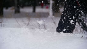 Uomo che cammina nella neve profonda nella foresta di inverno al giorno di Snowy Movimento lento archivi video