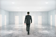 Uomo che cammina nella sala con le porte Immagine Stock Libera da Diritti