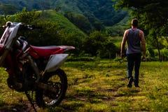 Uomo che cammina a partire dalla bici della sporcizia in montagne guatemalteche immagine stock libera da diritti