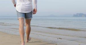Uomo che cammina per innaffiare sulla spiaggia, retrovisione delle gambe della parte posteriore maschio del primo piano video d archivio