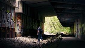 Uomo che cammina sotto il passaggio con i graffiti stock footage