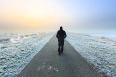 Uomo che cammina su un raod desolato vuoto Fotografia Stock Libera da Diritti
