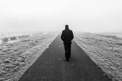 Uomo che cammina su un raod desolato vuoto immagine stock libera da diritti