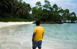 Uomo che cammina su una spiaggia Fotografie Stock