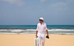 Uomo che cammina su una spiaggia con bagagli Immagine Stock