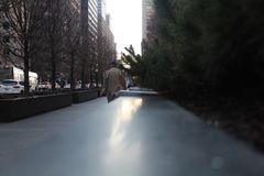 Uomo che cammina sul cappotto d'uso di inverno del marciapiede fotografie stock
