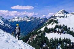 Uomo che cammina sulla cima innevata della montagna con le belle viste fotografia stock