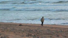 Uomo che cammina sulla spiaggia archivi video