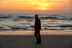 Uomo che cammina sulla spiaggia in Katwijk al tramonto netherlands fotografia stock