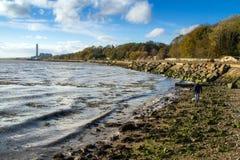 Uomo che cammina sulla spiaggia rocciosa fotografie stock