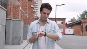 Uomo che cammina sulla via e che usando Smartwatch archivi video