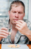 Uomo che cattura le pillole Immagini Stock Libere da Diritti