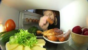 Uomo che cerca alimento nel frigorifero La scelta fra carne o le verdure stock footage