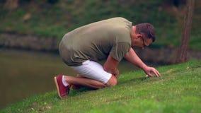 Uomo che cerca nella breve erba sulla banca di uno stagno archivi video