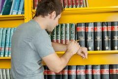 Uomo che cerca un libro Immagine Stock Libera da Diritti
