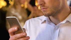 Uomo che chiacchiera sul telefono al partito, la gente che balla e che si diverte sul fondo stock footage