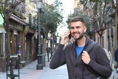 Uomo che chiama dal telefono e che distoglie lo sguardo all'aperto Immagini Stock