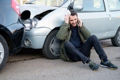 Uomo che chiama pronto soccorso dopo l'incidente stradale Immagine Stock Libera da Diritti