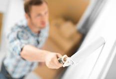 Uomo che colora la parete con il rullo Immagini Stock Libere da Diritti