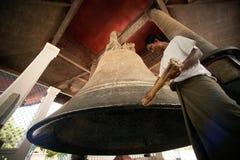Uomo che colpisce la campana di Mingun nel Myanmar immagine stock