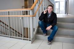 Uomo che comunica sul suo telefono delle cellule nel pozzo delle scale Fotografia Stock Libera da Diritti