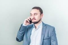 Uomo che comunica sul telefono Colloqui dell'uomo d'affari Fotografie Stock