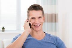 Uomo che comunica sul telefono mobile Immagine Stock