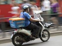 Uomo che conduce il motorino di consegna nel traffico cittadino Immagini Stock Libere da Diritti