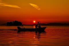 Uomo che conduce una barca con il tramonto nei precedenti fotografie stock