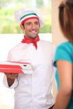 Uomo che consegna le pizze fresche Fotografia Stock
