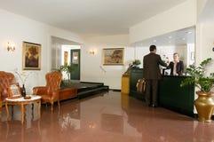 Uomo che controlla alla ricezione dell'hotel Immagine Stock Libera da Diritti