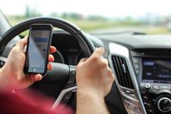 Uomo che controlla i suoi messaggi di testo mentre guidando Mandare un sms pericoloso nel concetto dell'automobile immagini stock libere da diritti