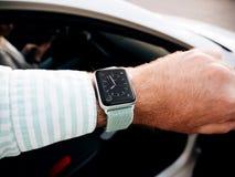 Uomo che controlla tempo sull'orologio di Apple Fotografie Stock