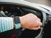 Uomo che controlla tempo sull'orologio di Apple Immagine Stock