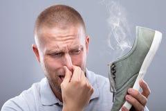 Uomo che copre il suo naso mentre tenendo scarpa puzzolente fotografie stock