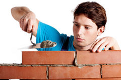 Uomo che costruisce una parete Immagini Stock