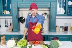Uomo che cucina alimento salutare in pieno della vitamina Alimento biologico per l'uomo in buona salute Negozio bio Metta una cer immagini stock