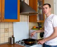 Uomo che cucina alla cucina Fotografie Stock Libere da Diritti