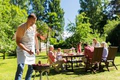 Uomo che cucina carne sulla griglia del barbecue al partito di estate Fotografie Stock Libere da Diritti