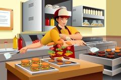Uomo che cucina gli hamburger Fotografia Stock