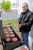 Uomo che cucina gli hamburger su un BBQ Immagine Stock