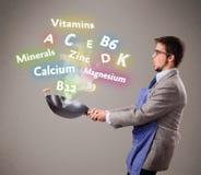 Uomo che cucina le vitamine ed i minerali immagini stock