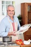 Uomo che cucina pasto immagini stock