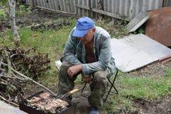 Uomo che cucina pesce gatto Fotografia Stock Libera da Diritti