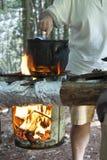 Uomo che cucina pranzo su fuoco di accampamento Fotografie Stock