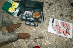 Uomo che cucina salmone reale su una griglia di campeggio fotografia stock libera da diritti